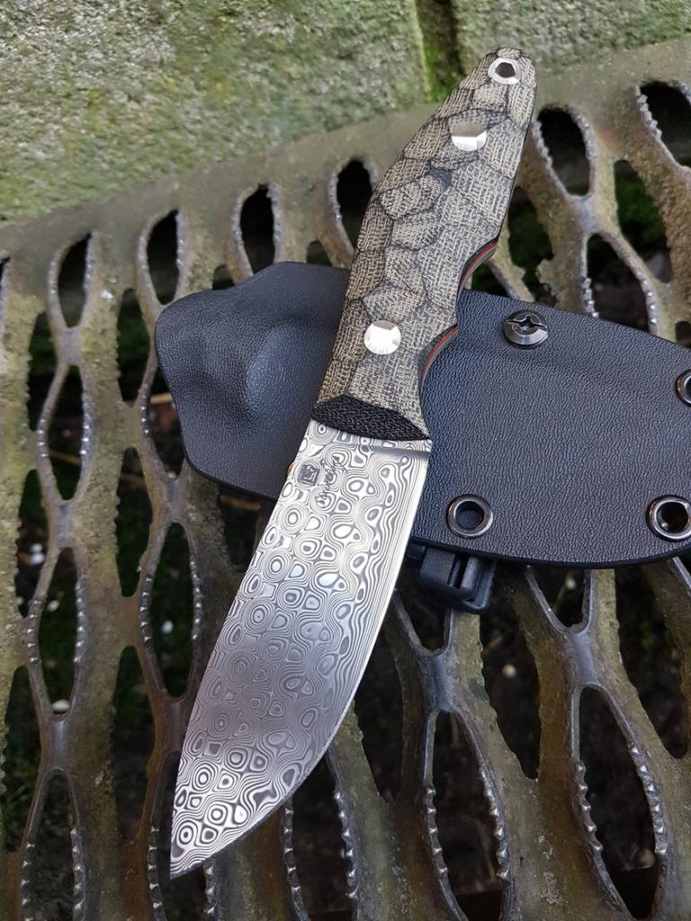 Gorgeous Rose pattern Damasteel skinner with black micarta and red liners.